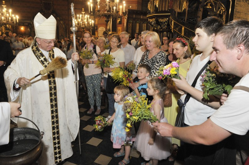 Abp Marek Jędraszewski święci przyniesione przez wiernych bukiety z ziół i kwiatów.    Fot.: A. Bujak