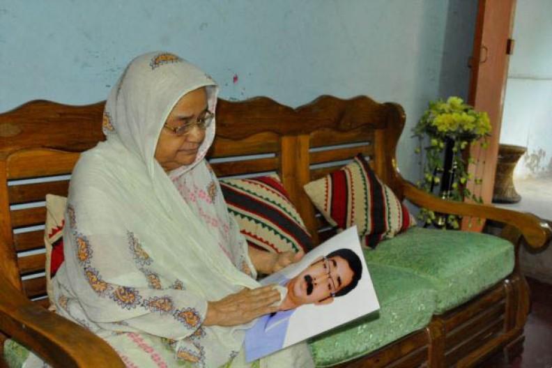 Matka trzymająca fotofragię zaginionego syna. Bangladesz.   Fot.: VOA/Wikimedia Commons