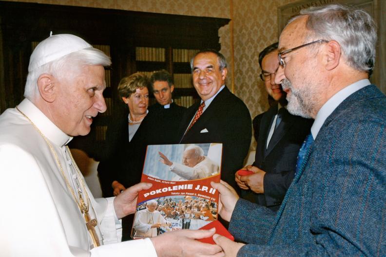 Papież Benedykt XVI przyjmuje na audiencji fotografa papieskiego Adama Bujaka, który prezentuje mu swoją książkę