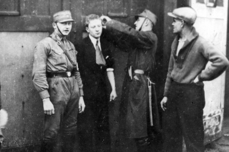 Funkcjonariusz SA przystrzyga włosy młodemu Żydowi. Fot.: NAC