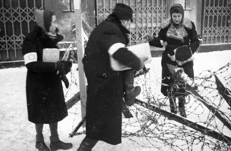 Dwoje Żydów przechodzi przez zasieki z drutów kolczastych w getcie. Fot.: NAC