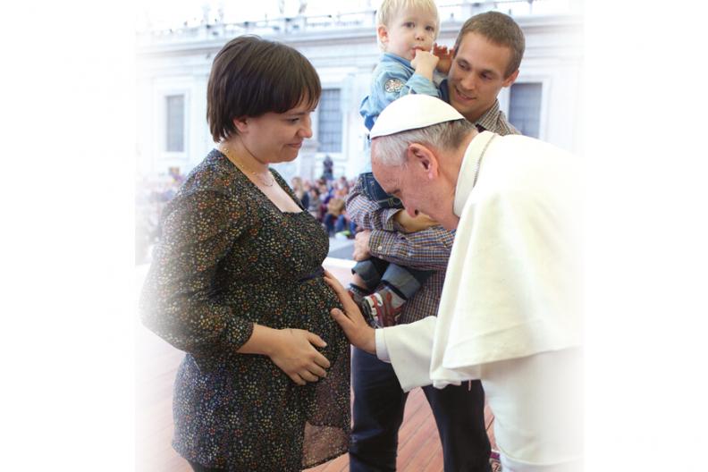 Papież Franciszek błogosławi dziecko w brzuchu jego mamy przed Bazyliką św. Piotra w Rzymie podczas spotkania modlitewnego w Dzień Rodziny, zorganizowanego w Roku Wiary 26 października 2013 r. Źródło: L Osservatore Romano