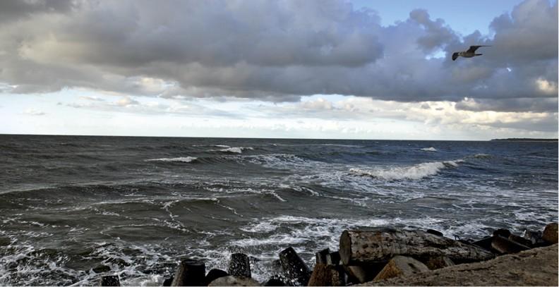 Groźnie zachmurzone niebo i powoli wzbierające fale na darłowskim odcinku wybrzeża Morza Bałtyckiego.