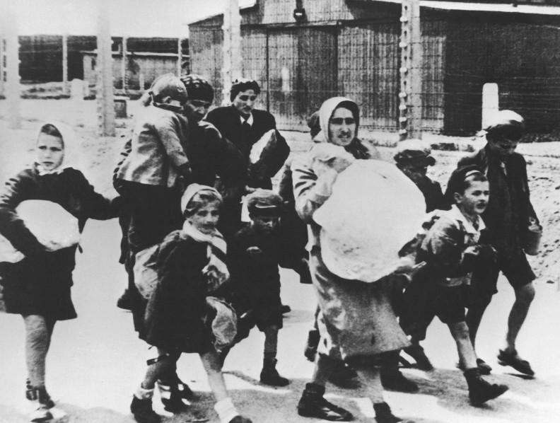 Auschwitz II – Birkenau.  Kobiety i dzieci prowadzone  po selekcji w kierunku komór gazowych i krematoriów nr IV i V.  (Fot. SS, 1944 r.)